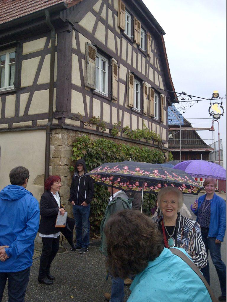 Ruth Römpert führt durch Oberacker, im Hintergrund das ehem. Gasthaus zum Löwen, die freundliche Frau mit der schönen Kette und dem Schirm ist Karin Coordes, davor mein Hinterkopf ;-)
